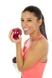 L латинская женщина спорта в одеждах фитнеса есть усмехаться плодоовощ яблока счастливый в здоровом питании Стоковое Изображение RF