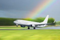 L'aéroport d'avion enlèvent sous la pluie sur un fond un arc-en-ciel Photos libres de droits