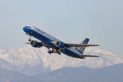 L'aéroport international de départ d'United Airlines Boeing 757 Los Angeles avec la neige a couvert des montagnes à l'arrière-pla Photos stock