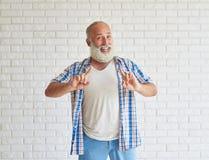 L'aîné élégant heureux dirige le doigt avec les deux mains Image libre de droits