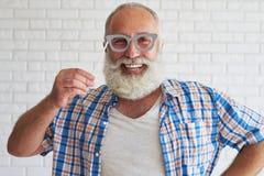 L'aîné élégant heureux est chemise essayent le verre-masque et le s gris Images libres de droits