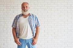 L'aîné élégant heureux habillé dans des jeans avec la chemise à carreaux est St Photos stock