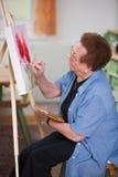 L'aîné actif peint un tableau dans les loisirs Image stock