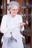 L'aîné actif polit des verres Photo libre de droits
