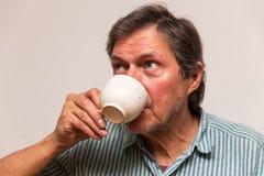 L'aîné boit une tasse de café Image stock