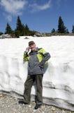 L'aîné dans les montagnes avec la neige de ressort Photographie stock libre de droits