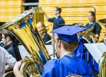 L'aîné de graduation de lycée joue le klaxon dans la bande dans le chapeau et la robe Photos libres de droits