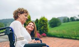 L'aîné a dissatisfait la femme dans un fauteuil roulant avec sa fille Image stock