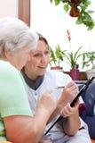 L'aîné et l'infirmière s'asseyent ensemble et écrivent des données Photo libre de droits