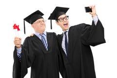 L'aîné et le type dans l'obtention du diplôme habille prendre un selfie Image libre de droits