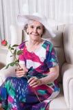 L'aîné féminin actif avec s'est levé dans sa main Photo libre de droits