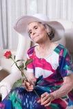 L'aîné féminin actif avec s'est levé dans sa main Photo stock