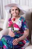 L'aîné féminin actif avec s'est levé dans sa main Image libre de droits