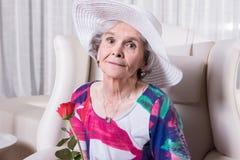 L'aîné féminin actif avec s'est levé dans sa main Image stock