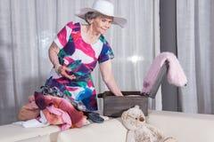 L'aîné féminin actif emballe la valise de vintage pour des vacances d'été Photographie stock