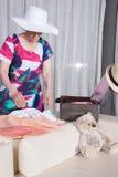 L'aîné féminin actif emballe la valise de vintage pour des vacances d'été Photo libre de droits