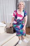 L'aîné féminin actif emballe la valise de vintage pour des vacances d'été Images stock