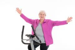 L'aîné féminin avec des bras s'exercent avec la machine de forme physique Photo stock