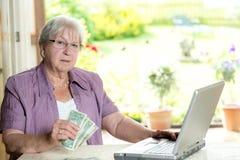 L'aîné féminin avec l'argent utilise l'ordinateur Photos libres de droits