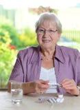 L'aîné féminin avec la médecine sourit Images libres de droits