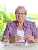 L'aîné féminin avec la médecine sourit Photographie stock libre de droits