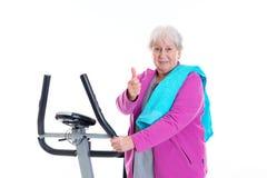 L'aîné féminin avec le pouce s'exercent avec la machine de forme physique Photographie stock libre de droits