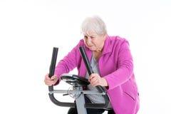 L'aîné féminin avec le pouce s'exercent avec la machine de forme physique Photos stock