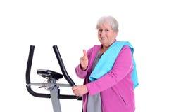 L'aîné féminin avec le pouce s'exercent avec la machine de forme physique Images stock