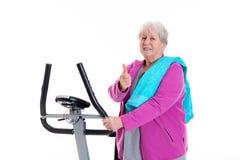 L'aîné féminin avec le pouce s'exercent avec la machine de forme physique Photographie stock