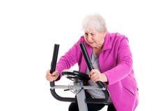 L'aîné féminin avec le pouce s'exercent avec la machine de forme physique Image libre de droits
