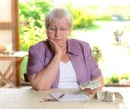 L'aîné féminin calcule son budget Image stock