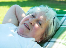 L'aîné féminin détend dans le jardin Photos libres de droits