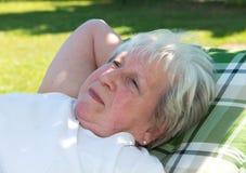 L'aîné féminin détend dans le jardin Image stock