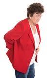 L'aîné féminin d'isolement en rouge a le mal de dos ou le rhumatisme Photos stock