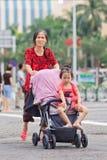 L'aîné féminin pousse babycar avec la petite-fille, Zhuhai, Chine Photographie stock libre de droits