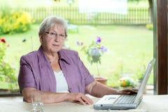 L'aîné féminin utilise l'ordinateur Images stock