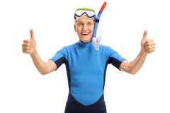L'aîné gai avec l'équipement naviguant au schnorchel faisant des pouces lèvent le signe Photographie stock