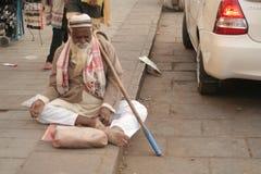 L'aîné indien a physiquement contesté l'aide de recherche d'homme/prier se reposer sur une route à grand trafic Photographie stock libre de droits