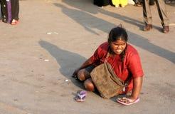 L'aîné indien a physiquement contesté l'aide de recherche de femme/prier se reposer sur une route à grand trafic Photographie stock