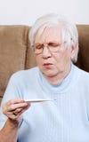 L'aîné malade a choqué sa température sur le thermomètre Photos libres de droits
