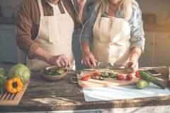 L'aîné a marié des couples faisant cuire la nourriture saine avec la musique Photo stock