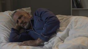 L'aîné ne peut pas tomber endormi, épuisé par de mauvaises pensées et souvenirs tristes, insomnie Image stock