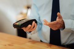 L'aîné a occupé l'homme tenant le distributeur automatique de billets et gesticulant Photographie stock libre de droits