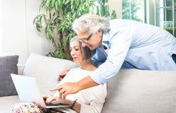 L'aîné a retiré des couples utilisant l'ordinateur portable à la maison sur le sofa - EL image stock