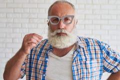 L'aîné sérieusement élégant essaye le verre-masque et le sourire gris Images stock