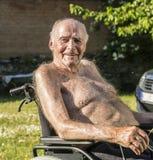 L'aîné s'assied dans la chaise dans le jardin Images libres de droits