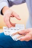 L'aîné traitent avec des médicaments avec des pilules à la maison Images libres de droits