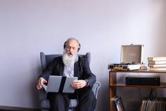 L'aîné travaille à l'ordinateur et apprécie la musique sur des écouteurs  Photographie stock