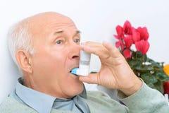 L'aîné a vieilli l'inhalateur d'utilisations d'homme pour traiter son mal Photo libre de droits