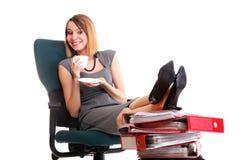 Le gambe di rilassamento della donna di affari di sciopero della donna aumentano l'abbondanza del documento Immagini Stock Libere da Diritti